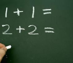 Hand writing simple mathematical sums on a chalkboard or blackboard in a kindergarten school teaching children basic addition