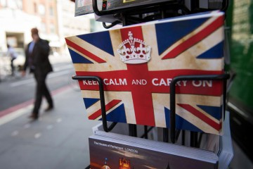 """Postcards featuring the World War II British slogan """"Keep Calm and Carry On"""" are seen outside a newsagents in London, on 24 June, 2016.  Britain voted to break away from the European Union on June 24, toppling Prime Minister David Cameron and dealing a thunderous blow to the 60-year-old bloc that sent world markets plunging."""