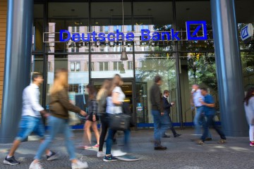 Pedestrians walks past a Deutsche Bank AG bank branch in Berlin, Germany, on Tuesday, Sept. 27, 2016. Deutsche Bank AG rose in Frankfurt trading after the German lender agreed to sell its U.K. insurance business for 935 million euros ($1.2 billion) and Chief Executive Officer John Cryan ruled out a capital increase. Photographer: Krisztian Bocsi/Bloomberg