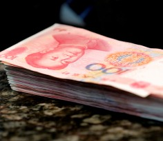 Chinese 100 yuan banknotes are seen on a counter of a branch of a commercial bank in Beijing