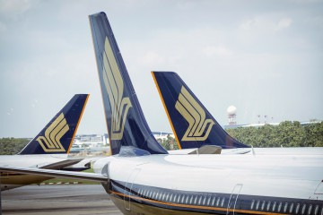 Singapore Airlines Ltd. aircraft sit at Changi Airport in Singapore, on Thursday, March 3, 2016. Singapore Air, hurt by competition from opulent Middle Eastern carriers and a rash of budget airlines, is trying to revive its fortunes the way it knows best: wooing flyers with new aircraft. While the new aircraft with its extra-wide cabins and a new entertainment system will set Singapore Air apart from local rivals, it might be too little, too late to turn around its fortunes. Photographer: Bryan van der Beek/Bloomberg