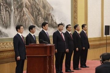 Members of the Communist Party of China's new Politburo Standing Committee Han Zheng, from left, Wang Huning, Li Zhanshu, Xi Jinping, China's president, Li Keqiang, Wang Yang and Zhao Leji stand on stage in the East Hall of the Great Hall of the People in Beijing, China, on Wednesday, Oct. 25, 2017. Chinese President Xi Jinping unveiled a new leadership line-up that included no clear potential heirs, breaking with a quarter-century-old succession system and raising the chances that he might seek to stay in office beyond 2022. Photographer: Qilai Shen/Bloomberg