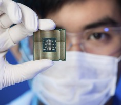 Cropped image of an engineer showing a computer microchip on the foreground