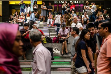 People sit on a set of steps on Orchard Road in Singapore, on Sunday, Dec. 16, 2016. Shopping has overtaken gambling as the biggest earner in Singapore's tourism industry for the first time since 2012, surging 44 percent in the six months through June from a year ago, official data show. Photographer: Sanjit Das/Bloomberg via Getty Images