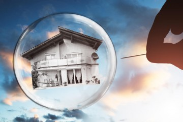 Human-Hand-Poking-House-And-Bubble-With-Needle-Against-Cloudy-Sky